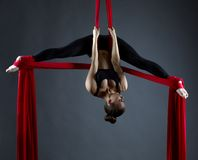 Sexy female acrobat performs hanging upside down Stock Photos