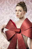 Sexy female adorned like a gift. Sensual woman with elegant blonde hair-style posing in christmas shoot with big red glitter bow covering her naked breast Royalty Free Stock Images