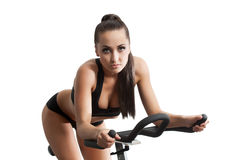 Sexy female athlete exercising on stationary bike Stock Images