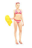 Sexy female in bikini holding a yellow swimming float Royalty Free Stock Photography
