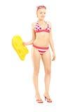 Female in bikini holding a yellow swimming float. Full length portrait of a female in bikini holding a yellow swimming float, isolated on white background royalty free stock photography