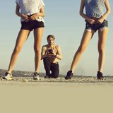 Female bodies and legs in shorts and sport shoes. Sexy, female bodies and legs in shorts and sport shoes posing on sunny day. Fit man, handsome macho or royalty free stock image