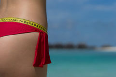 Sexy female buttocks with a tape measure on the beach. The conce. Pt of diet and healthy lifestyle Stock Photo