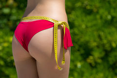 Sexy female buttocks with a tape measure on the outdoor. The con. Cept of diet and healthy lifestyle Stock Image