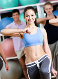 Female coach trains with her group. Female coach exercises with her group at the gym in a fitness class helping them to loose weight royalty free stock photography