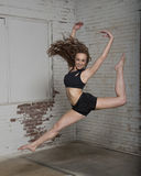 Female dancer in industrial studio. Young red haired woman dancer leaps in warehouse studio setting in black top and shorts - barefoot classical dance stock images