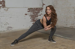 Female dancer in industrial studio. Young red haired woman dancer poses in warehouse studio setting in baggy pants and black top - hip-hop or urban feel royalty free stock image