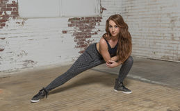 Female dancer in industrial studio. Young red haired woman dancer poses in warehouse studio setting in baggy pants and black top - hip-hop or urban feel royalty free stock photography