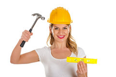 Sexy female engineer with a hammer and a spirit-level in her han Stock Photo