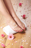 Sexy female feet, a white towel and petals on the floor Stock Photo