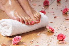 Sexy female feet, a white towel and petals on the floor Royalty Free Stock Image