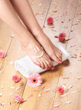 Sexy female feet, a white towel and petals on the floor Royalty Free Stock Photos