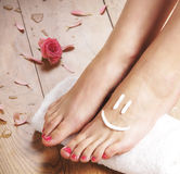 Sexy female feet, a white towel and petals on the floor Royalty Free Stock Photography
