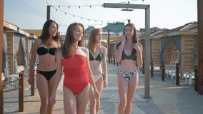 Sexy female friends with beautiful slender bodies happily spend time walking promenade of luxurious guesthouse during