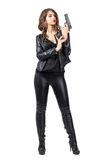 Female gangster girl reloading handgun cartridge. Full body length portrait isolated over white studio background stock image