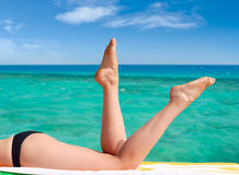 Sexy female legs. Against the turquoise sea background Royalty Free Stock Photography