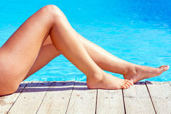 Sexy female legs at blue swimming pool Royalty Free Stock Image