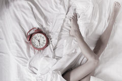 Sexy female legs with clock on bed in bedroom Royalty Free Stock Image