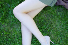 Sexy female legs on the grass Stock Images