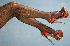 Female legs in high heel black shoes and fishnet stockings. On blue background royalty free stock images