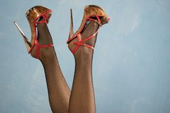 Female legs in high heel black shoes and fishnet stockings. On blue background royalty free stock image