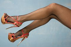 Female legs in high heel shoes and fishnet stockings. On blue background royalty free stock photos
