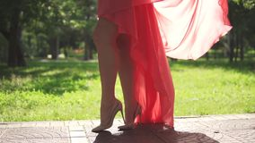 Sexy female legs in high heels closeup. a young girl in a dress waving in the wind. Slow motion. Sexy female legs in high heels closeup. a young girl in a dress stock video
