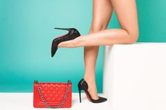 Female legs in high heels with red bag on a blue background. Female legs in high heels with red handbag on a blue background. - Image royalty free stock photography