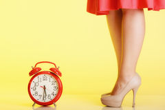 Sexy female legs in high heels and red clock. Time for femininity. Sexy female legs in beige high heels standing next to red clock on yellow background. Time Royalty Free Stock Photo