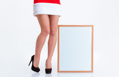 Sexy female legs in santa claus cloth and blank board Royalty Free Stock Photography