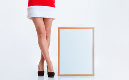 Female legs in santa claus cloth and blank board. Closeup portrait of a female legs in santa claus cloth and blank board on a white background royalty free stock image