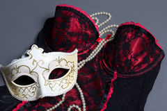 Sexy female lingerie, carnival mask and necklace on grey Stock Images