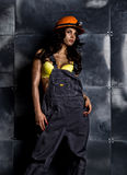 Sexy female miner worker with pickaxe, in coveralls over his naked body Stock Image