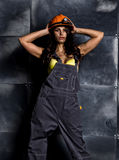 Sexy female miner worker with pickaxe, in coveralls over his naked body Royalty Free Stock Image