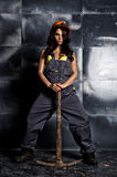 Sexy female miner worker with pickaxe, in coveralls over his naked body Royalty Free Stock Images