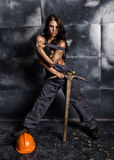 Sexy female miner worker with pickaxe, in coveralls over his naked body. erotic industry concept Royalty Free Stock Photos