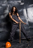 Sexy female miner worker with pickaxe, in coveralls over his naked body. erotic industry concept Stock Photography