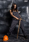 Sexy female miner worker with pickaxe, in coveralls over his naked body. erotic industry concept Royalty Free Stock Images