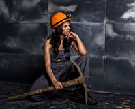 Sexy female miner worker with pickaxe, in coveralls over his naked body, sitting on the floor on backdrop of steel wall Royalty Free Stock Photography