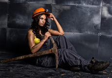 Sexy female miner worker with pickaxe, in coveralls over his naked body, sitting on the floor on backdrop of steel wall Royalty Free Stock Photos