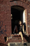 Sexy female model in black dress posing with legs apart against brick frame building Stock Image