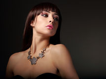 Sexy female model in fashion necklace on dark Stock Images