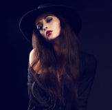 Sexy female model posing in black shirt and elegant hat with red Stock Photography