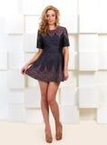 Female model in short dress. Near futuristic wall stock photos