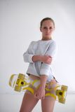 Sexy female model with yellow skateboard on white background Stock Image