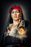 Sexy female pirate shooting from gun. Portrait of sexy female pirate shooting from an old pistol Stock Photo