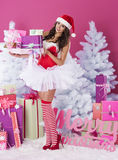 Sexy female santa claus. Sexy santa claus with stack of christmas presents Stock Photos