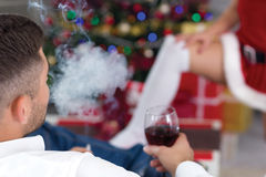 Female Santa seduces man on Christmas Eve. Women santa seduces man royalty free stock photography