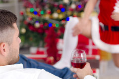 Sexy female Santa seduces man on Christmas Eve Stock Photography