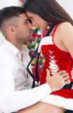 Sexy female Santa seduces man on Christmas Eve Royalty Free Stock Photos